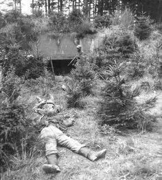 Two German soldiers killed in action lie outside a well-camouflaged bunker in Germany knocked out by troops of the U.S. 22nd Infantry, 4th Infantry Division on September 15, 1944.