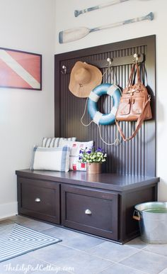 Nautical entryway with life preserver ring (just for the fun of it), framed signal flag art and boat paddles. Browse more Nautical Decor on Completely Coastal: http://www.completely-coastal.com/search/label/Nautical%20Decor%20Ideas