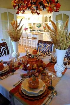 table runner in fall leaves colors, wheat head table centerpieces and chandelier decorated with leaves