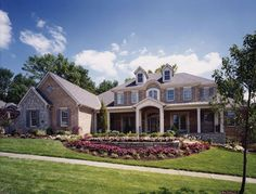 The Brick and stone exterior showcases a stately colonial entry with sidelights and a large front porch of this luxury home.  House Plan # 161044.