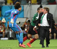 Keeping up: Mexican goalkeeper Guillermo Ochoa ran to his manager and leapt on him to celebrate