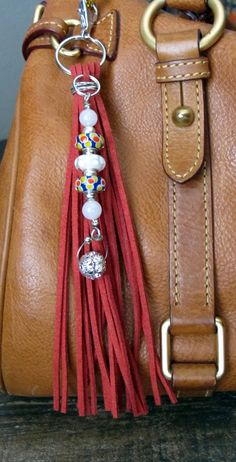 #ThePaintedCabeza ~ This handmade tassel charm can be used on your purse, backpack, zipper, wherever youd like to add some charm! Its made up of red suede, lampwork glass beads, silver plated beads, and a silver crystal bling bead. Altogether, the charm is approximately 8 long.