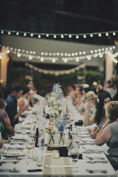 farm style dining at wedding - fairy lights and jars filled with pretty blooms