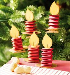 """Great ornament for our """"old fashioned"""" christmas tree this year! Folded strips of paper, flame, glued to circle of cardboard or stiff paper with a clothes pin glued under for attaching to the tree. *no link to directions, just a photo More"""