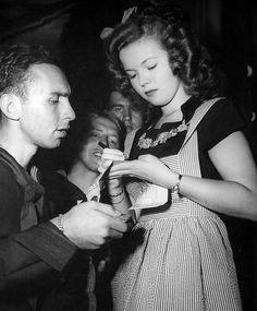 Shirley Temple autographs a Short Snorter Bill belonging to Mate First Class Bernard Abramson at the Stage Door Canteen in San Francisco