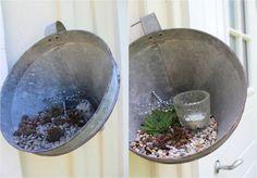 arrangement décoratif dans un entonnoir métallique composé de cailloux, plantes succulentes, bougie chauffe-plat et figurine libellule
