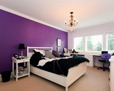 bedroom with dark purple accent wall and chandelier