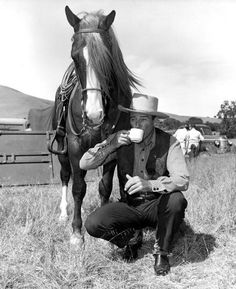 Tall in the Saddle - John Wayne has a cup of coffee on location - The horse belongs to then-stunt man Ben Johnson who rode this horse in three John Ford movies.
