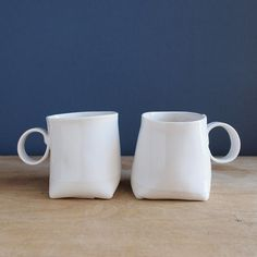 These cups are made with thin porcelain slabs of clay, cut and folded to form a pillow like shape. Glazed with a satin white glaze, one cup