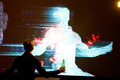 This projection installation uses full body motion capture to recreate an abstract form of the person standing in front of it. In a 3D particle engine, it detects when a user is standing in front of it and using facial and body recognition adds glasses and a heart to the user's body.