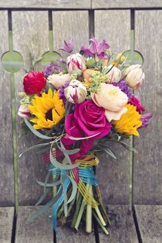 Absolutely adore the bright colors in this fun bouquet. We all know anything involving sunflowers is my dream come true.   Fun & Colourful Vintage Carnival Wedding Ideas see more at http://www.wantthatwedding.co.uk/2015/05/29/fun-colourful-vintage-carnival-wedding-ideas/