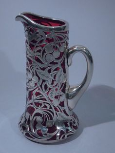 "Cranberry glass jug with sterling silver overlay, C 1900. The jug has a flared bottom, straight sides, and scroll handle. Overlay with foliage and cherries. Engraved monogram (""R"") on cartouche. Rim and handle are silver. Nice size with unusual cherry motif."
