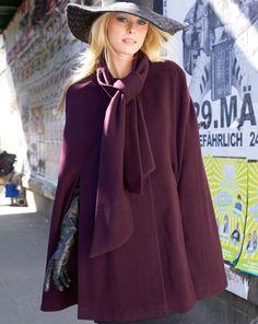 Cape mit (angeschnittenem) Schal sowie hohe Schlitze vorne und hinten.