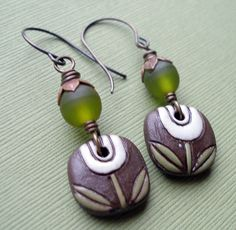 earrings by Lorelei Eurto,featuring a polymer clay floral bead (made by Golem studios) at the bottom in purple.