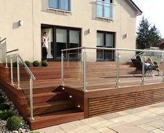 Balau hardwood deck in Glasgow with glass and stainless steel balustrade, buxus ball topiary and sandstone paving