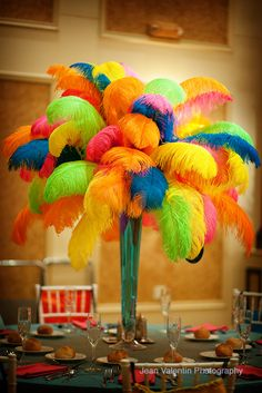 Colourful feather centerpiece. Do you want ideas on how to stay within YOUR wedding budget? ... 'The Gold Wedding Planner' iPhone App - everything you need to 'know & do' to plan your dream wedding. For more information & free tips visit www.aprofessionalorganiser.com.