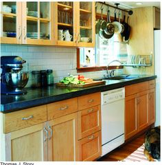 Wall mounted drying rack, Pots above sink, glass cabinet panes... love.