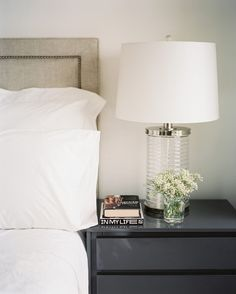 Lonny: Crisp white bed linens are offset by a dark gray bedside table that gives a substantial lamp pride of place.