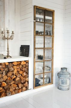 Logging | My Paradissi | built-in wood storage and cabinet made with salvaged window. Linen closet door? A mirror could add light and make your room look larger.