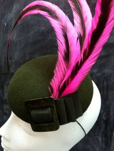 Pink feathered punk style cocktail hat with military green felt base and vintage buckle. Hand made by fifilabelle in London.