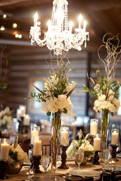 Love these tall centerpieces with the candles and chandeliers! #BridesofOK