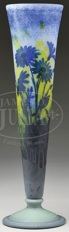 James D. Julia, Inc. -  Daum Nancy French Cameo Vase. Large trumpet vase has a blue, white and yellow mottled ground and is decorated overall with cornflower pattern in various stages of bloom. The vase is supported by an inverted saucer stepped foot of light green glass with matching conflower design in relief