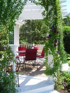 Twining vines of clematis soften the hardscaping and add a burst of color to this outdoor room.