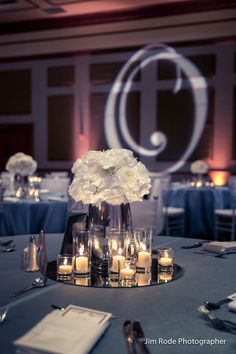 Another wedding table centerpiece at the Ruthe Jackson Center. Silver and white theme with a silver gobo light projection. Lighting Randy Ro Entertainment, photo Jim Rode Photographer.