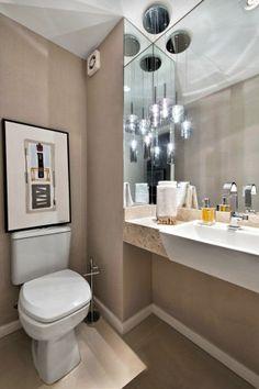 No lavabo, o pendente faz um jogo de reflexos com o espelho. E o quadro foi parar em cima do vaso sanitário.