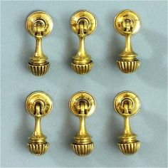 A set of 6 reclaimed antique or vintage solid cast brass drop handles. Suitable for cabinet doors or drawers up to 2 cm thick. Complete with original backplates and square securing nuts.