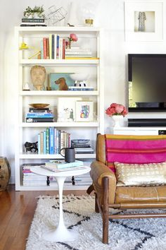 Colorful interiors. Old tan leather chair with pink throw, white side table and a black-and-white kilim rug. Although the book shelf is packed with small items and books it doesnt seem too cluttered.