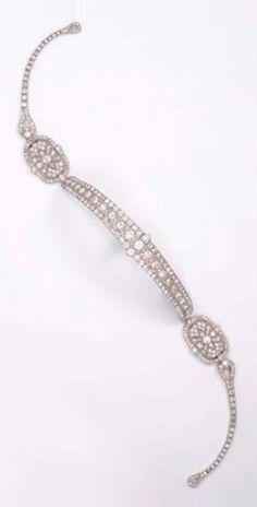 CARTIER - A FINE ART DECO METAMORPHIC DIAMOND BANDEAU, CIRCA 1925. The central part forming a brooch/bracelet, also forming a choker necklace with the diamond line sides, the side panels forming a pendant necklace, one oval panel forming a brooch, with French assay marks for platinum, signed Cartier, Paris, London, New York. #Cartier #ArtDeco