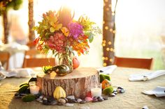 For our center pieces we used burlap overlays, and placed a wood disc in the center to hold up the floral arrangement. We then add some stones, moss, and oddly shaped gords to give it that harvest feel.