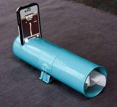 """Pringle Can Amplifier DIY:   Cut somewhat smaller hole for phone 1.5 inches from end of can, tape medium binder clip to each side of can, half way up. Spray paint entire thing if desired. Insert 15"""" piece of squished toilet paper into open end of tube. Play phone."""