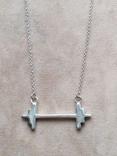 A modern take on the barbell necklace.