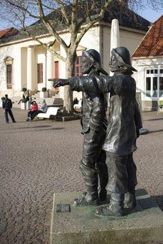 #Neustadt/Holstein Zwei Fischer in wetterfester Arbeitskleidung stehen eng beeinander, einer mit den Händen in den Taschen, einer mit nach vorn gestreckter, wegweisender Hand. Beide schauen entschlossen mit festem Bl...