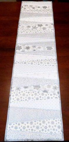 Dieser Tischläufer ist mit unterschiedlicher Breite Keile geschnitten aus einer Vielzahl von weißen und silbernen Baumwollstoffe, bieten einen Hauch von Eleganz zu Ihrem Esstisch zusammengesetzt. Es ist mit einem kostenlosen Silber Stoff gebunden und hat ein fester weißer Baumwolle auf der Rückseite verwendet. Zwischen den zwei äußeren Stoffen ist eine Schicht aus Baumwolle Vlies.  Jeder Keil ist mit der Maschine Quilten skizziert.  Die Läufer misst etwa 60 lang und ist 15 1/2 breit. Ein...