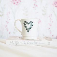 Livro Wildflower da Drew Barrymore em cima da cama branca com uma caneca com coração em cima. Ao fundo, fronhas com flores cor-de-rosa e verde. Composição romântica, clean e delicada.