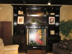 """Traditional Ent Center Price: $995.00  Item #: 41166 Is that an eye-catching piece or what! This black, traditional style entertainment center is sure to make a statement in your family or media room. It's 119"""" long x 30"""" deep x 110"""" high. Very large piece. This unit has a 47"""" wide cutout in the middle made for a projection screen TV. There are lights above in each section and two rows of glass shelves as well."""