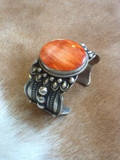 """Native American Orange Spiny Oyster Cuff     Looking at such beauty tells the capabilities of Native American art! This piece of Native American jewelry is Navajo hand crafted out of genuine sterling silver and real Orange Spiny Oyster Shell. The inner bracelet circumference measures approximately 5-1/4"""", plus a 7/8"""" opening, and 1-1/2"""" at widest point."""
