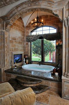 stone walls, giant bathtub, couch in bathroom, window to the garden