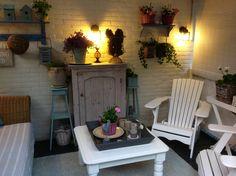 De veranda met kastje en bank van Marktplaats en plantentafeltjes / rekjes via de Kringloop.