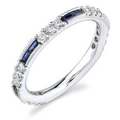 Features alternating clusters of round diamonds and channel set baguette sapphires. Clusters span 3/4 across ring. Ring is 2.5mm wide, with a total gemstone weight of 0.60 carats.