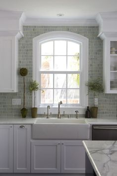 farmhouse sink, window, boxed in cabinet top instead of soffits, marble, grey and white