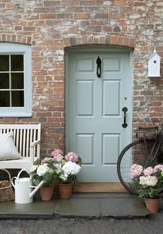 Duck-egg blue front door with pastel pink and white roses.