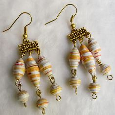 Handmade paper bead necklace, beads are made from yellow and orange multi-colored scrapbook paper with eye pins on a gold cable chain fastened with a gold toggle clasp. Earrings are dangle earrings with 6 paper beads each. Necklace Length: 18 1/2 circumference, hangs 5 1/2 Earrings: hang
