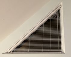 This triangular window uses a regular blind, cut into a triangle and mounted on the hypotenuse.:mildlyinteresting