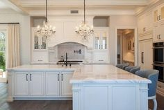 Elegant, well appointed white kitchen boasts an l-shaped white island accented with oil rubbed bronze fleur de lis pulls and a white marble countertop seating gray barrel back barstools and fitted with a sink and oil rubbed bronze faucet illuminated by two crystal chandeliers.