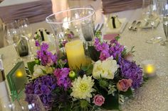 A Hurricane Lamp surrounded by fresh flowers