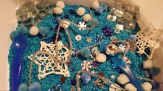 Winter wonderland theme sensory bin for my littles. My daughter and I dyed the rice. I then added snowflake gems, starched snowflake doilies,  pompoms, square glass gems, shiny silver icicle like pipe cleaners,  blue buttons, and blue spoons to scoop :)
